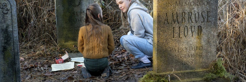 Flora und ihr Au-Pair Dani knien zwischen Grabsteinen. Flora hat zudem Malstift und Blätter vor sich liegen