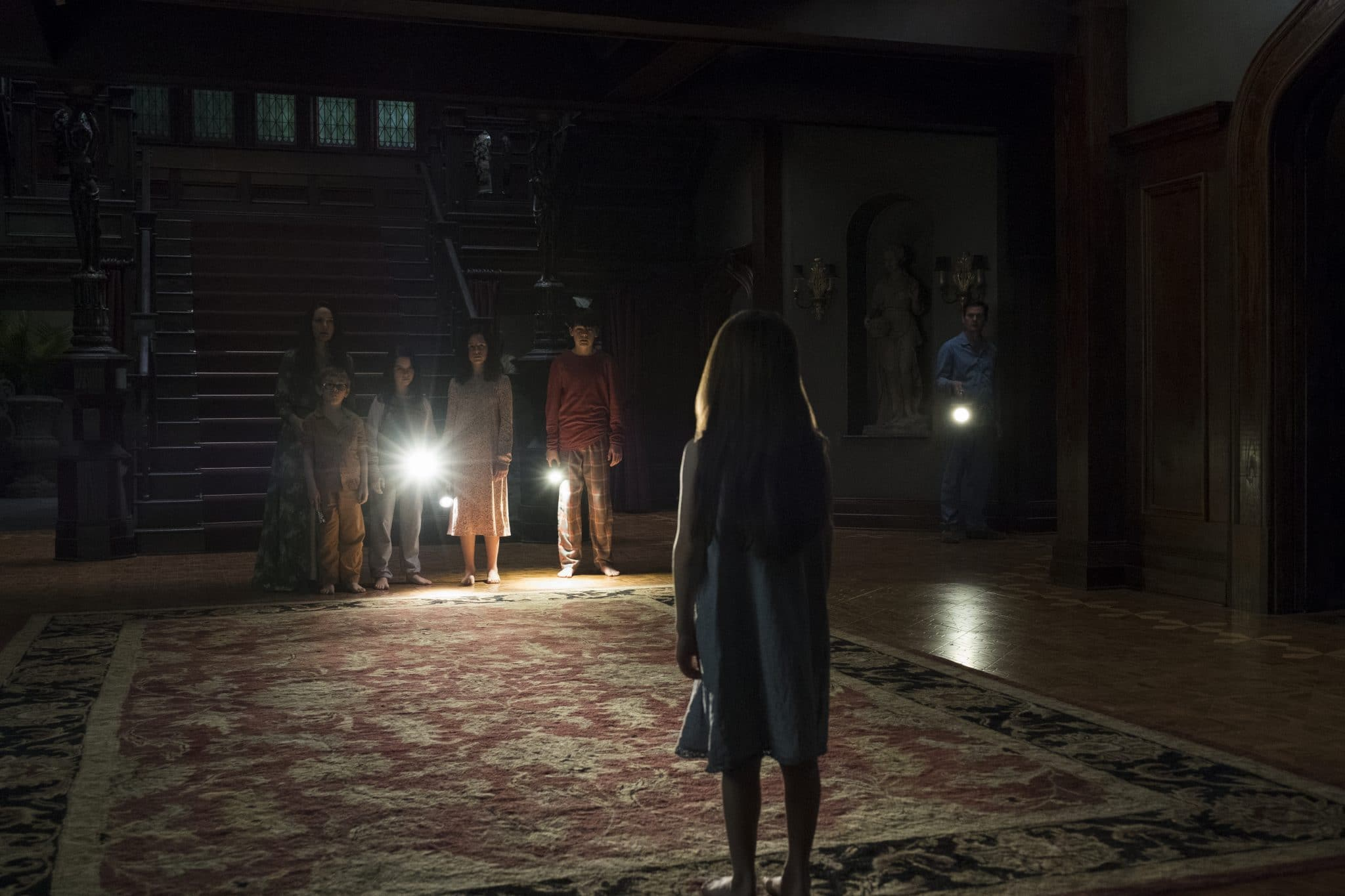 Ein Treppenhaus nur von Taschenlampen erhellt mit einem riesigen Teppich auf dem Boden. Man sieht ein kleines Mädchen von Hinten und hinten im Bild vier Kinder mit ihrer Mutter und ganz weit hinten einen weiteren Mann mit Lampe den Raum betreten.