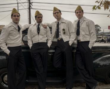 Die vier Crew-Mitglieder des Films treffen sich vor einem Auto an der Tankstelle