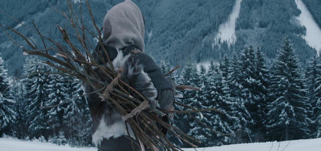 Albrun ist mit ein wenig Holz beladen und blickt auf die verschneiten Alpen, die als Kulisse Hagazussa zu einem der atmösphärischsten Hexenfilme aller Zeiten machen. © Indeed Film