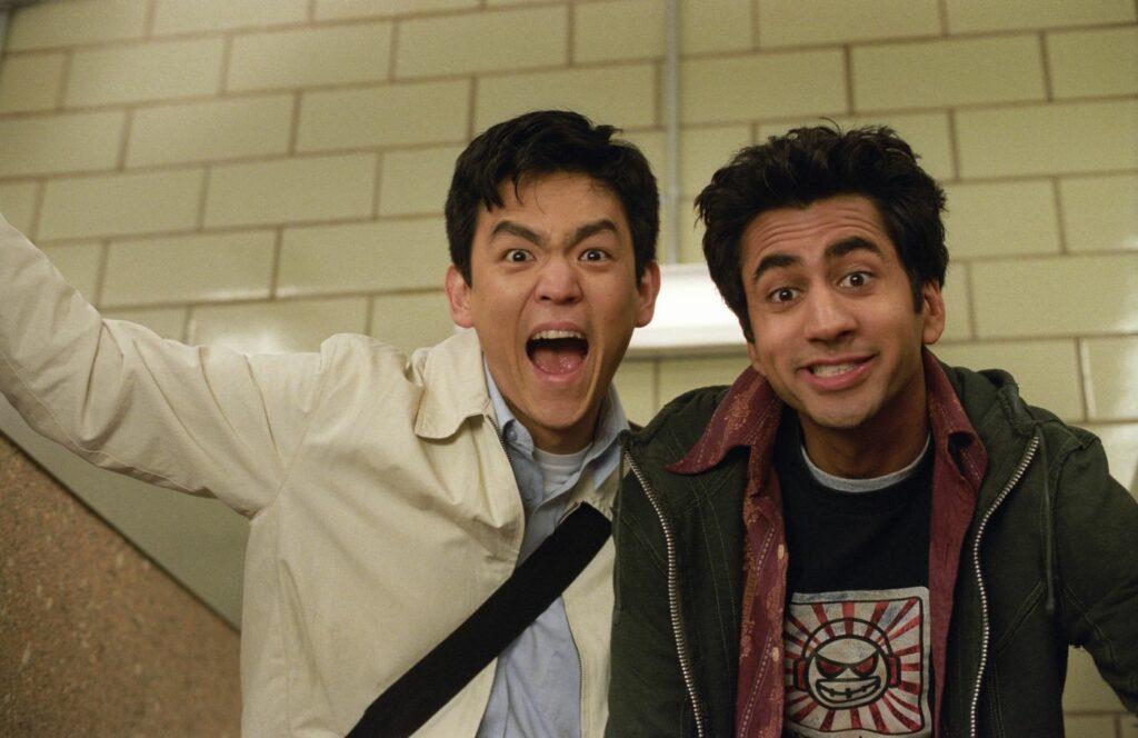 Harold und Kumar stehen vor einer weiß gekachelten Wand und sehen in die Kamera. Dabei sehen sie stoned aus und lachen.