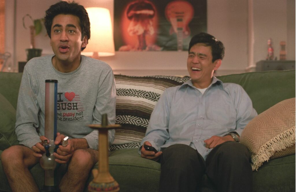 Harold und Kumar sitzen im Wohnzimmer auf der Couch und ziehen an einer Bong. Dabei haben sie eine Menge Spaß.