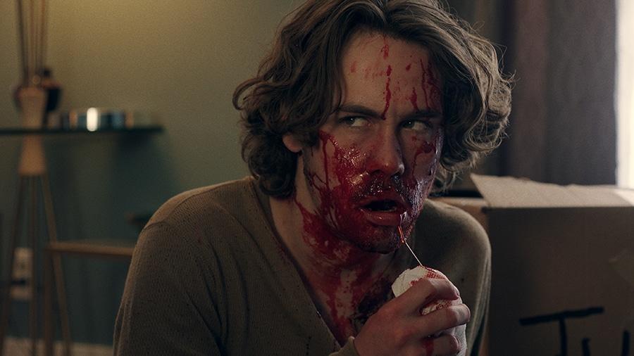 Jonah ist in einer Nahaufnahme in Harpoon zu sehen. Völlig blutverschmiert, hält er sich ein Tuch vor seinem Mund und blickt nach rechts.