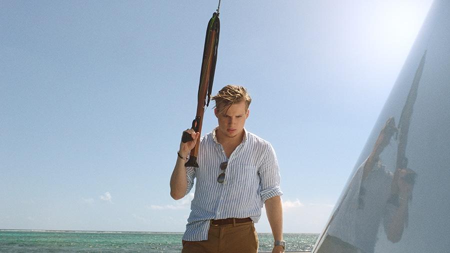 Vor dem Hintergrund des blaues Himmels und des Meeres ist Richard mittig im Bild positioniert. Er hält eine Harpune mit dem Unterarm zum Himmel gerichtet. Auf der rechten Bildseite ist ein Teil des Botes zu erkennen. Oberhalb der Bootsseite sind Sonnenstrahlen erkennbar