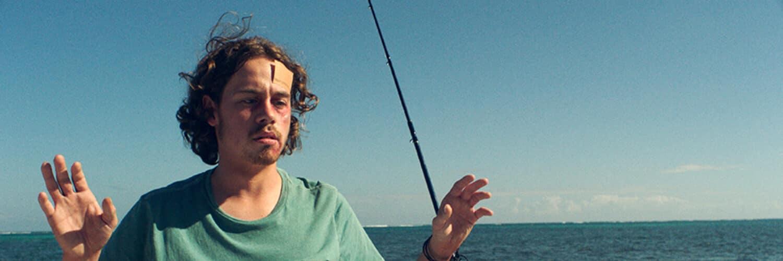 Jonas befindet sich auf der linken Bildseite und wird mit einer Harpune bedroht, die aus dem rechten Bildrand auf ihn gerichtet ist. Wehrlos der Mordabsicht ausgesetzt, hebt er seine Hände. Im Hintergrund ist das Meer und der Himmel zu erkennen.