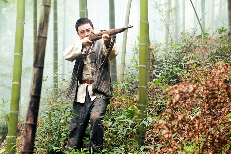 Jun (Shaoqun Lu) läuft mit einer Flinte im Anschlag durch einen Bambuswald.