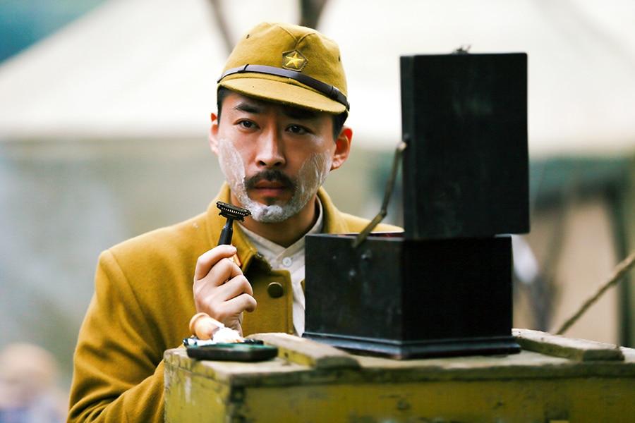 Shimamoto (Tsukagoshi Hirotaka) rasiert sich in Uniform vor einem kleinen Spiegel.