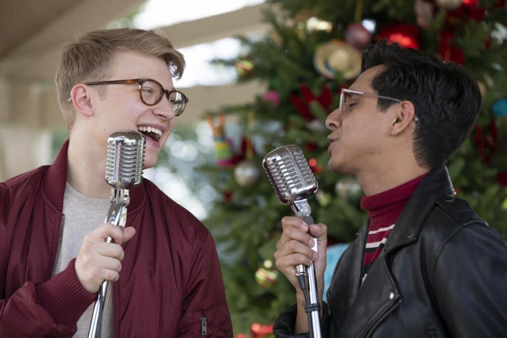 Zwei Sänger im Duett vorm Weihnachtsbaum, eine Szene aus High School Musical: The Musical: Holiday Special - Neu auf Disney+ im Dezember 2020
