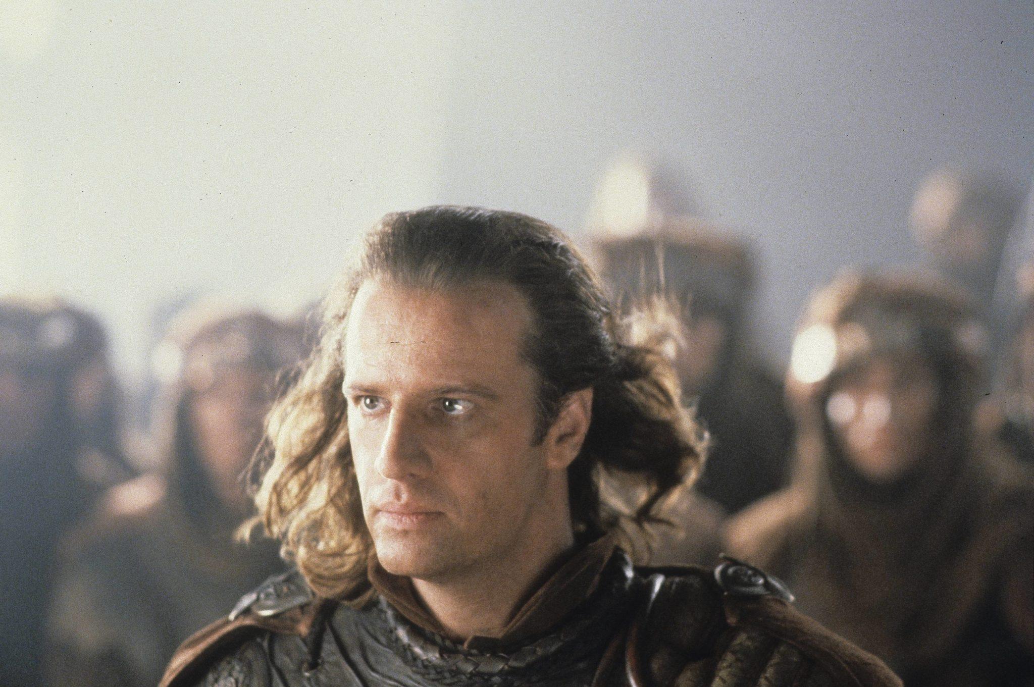 """Christopher Walken ist als Conor MacLeod mit langen Haaren und in altertümlicher Rüstung in """"Highlander II"""" in einer Gruppe von Kriegern zu sehen."""