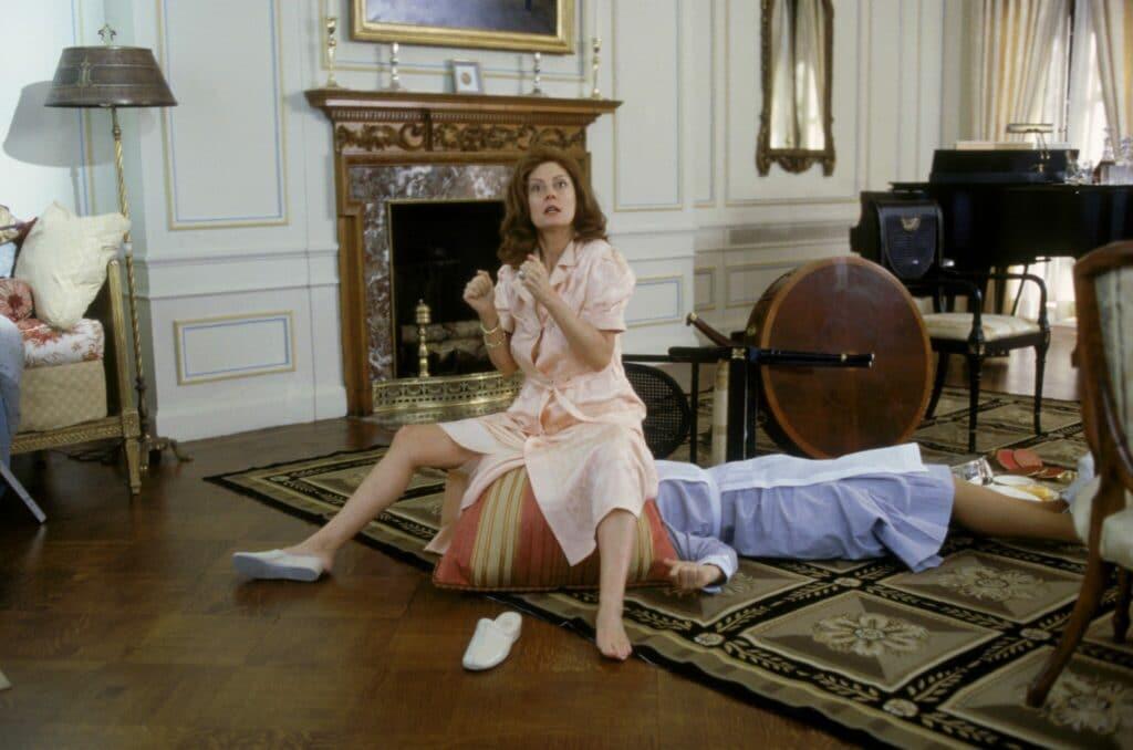 Igbys Mutter sitzt auf einem Kissen. Darunter die hilflose Haushälterin. Die Mutter hat ihren linken Schuh ausgezogen neben sich liegen. Im Hintergrund des vornehm gestalteten Wohnzimmers liegen ein runter Tisch und ein Stuhl umgestoßen.