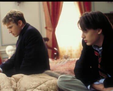 Igby sitzt auf der rechten Seite eines Bettes im Schneidersitz. Auf der Bettseite links neben ihm sitzt sein Bruder. Beide blicken in die linke Richtung.
