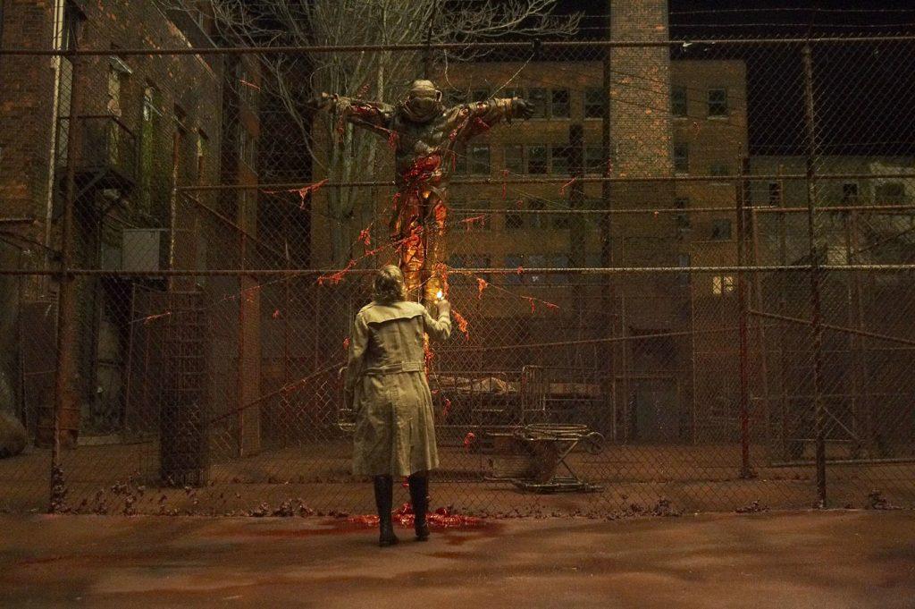 Radha Mitchell steht vor einer gekreuzigten Leiche an einem Maschendrahtzaun in Silent Hill