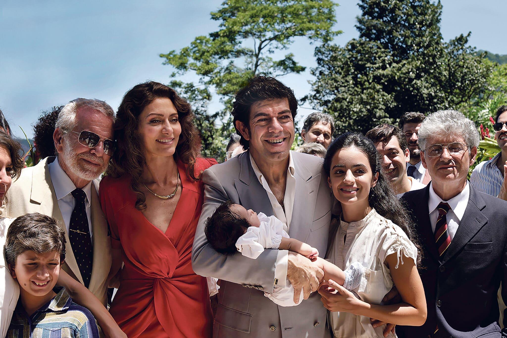 Tommaso Buscetta (Pierfrancesco Favino) hält in Il Traditore - Als Kronzeuge gegen die Cosa Nostra strahlend sein Baby auf dem Arm. Neben ihm stehen Maria (Maria Fernanda Cândido) und weitere Familienmitglieder.