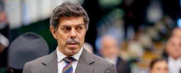 Tommaso Buscetta (Pierfrancesco Favino) steht in Il Traditore - Als Kronzeuge gegen die Cosa Nostra in grauem Anzug und blau-rot-gold-gestreifter Krawatte vor Gericht.