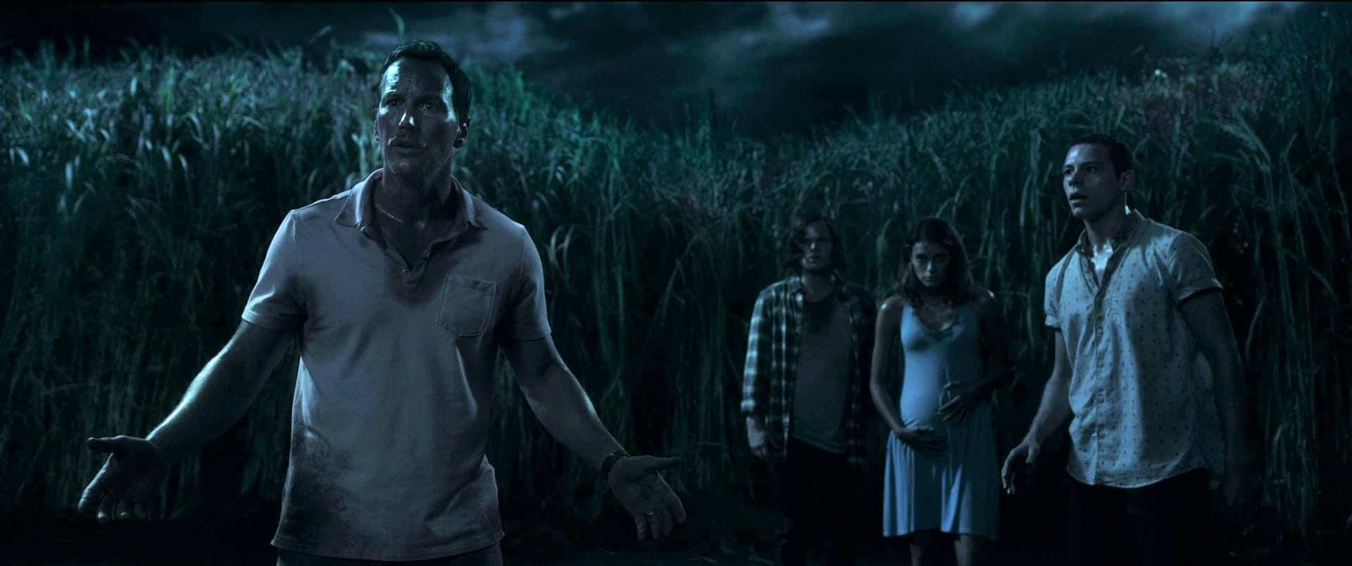 Patrick Wilson im Vordergrund mit erwartender Haltung. Im Hintergrund drei verängstigte Jugendliche und eine übermannshohe Reihe Grashalme