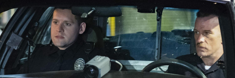 Nick Holland und Ray Mandel sitzen in ihrem Streifenwagen. Auf der Armatur liegt eine große Kamera die nach vorne filmt. Beide Polizisten ziehe eine ernste Miene.