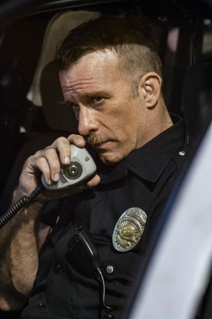"""Thomas Jane spielt in """"Im Netz der Gewalt"""" den LAPD-Veteran Ray Mandel. Das Bild zeigt ihn sitzend im Streifenwagen. Er hält in der rechten Hand den Polizeifunk in den er gerade reinspricht. Dabei schaut er leicht gedankenverloren aus dem Wagen heraus."""