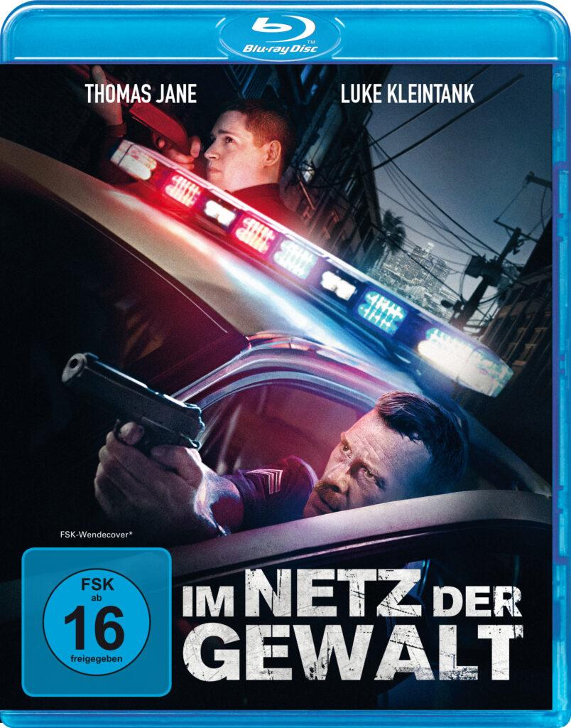 """Das deutsche Blu-ray Cover zu """"Im Netz der Gewalt"""" zeigt die beiden Hauptdarsteller Thomas Jane und Luke Kleintank, die beide mit Schusswaffe auf etwas Zielen. Dabei stehen sie hinter den Türen ihres Polizeiwagens in Deckung. Der Text """"Im Netz der Gewalt"""" steht in weißer, aber abgewetzt, im unteren Bereich des Covers."""