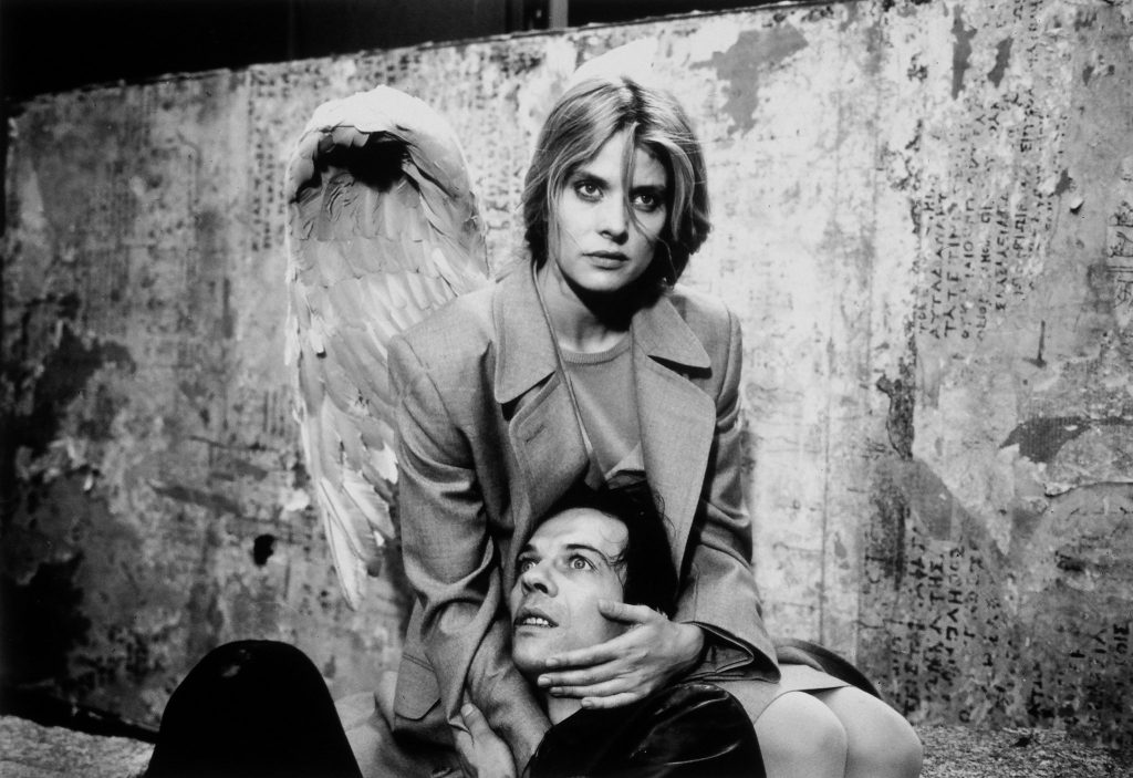 Raphaela, gespielt von Nastassja Kinski, an ihren Flügeln als Engel erkennbar, hält einen sterbenden und am Boden liegenden Menschen im Arm, um ihm den Übergang zu erleichtern. Sie kniet, ihr Blick ist nach vorn gerichtet. Der Mensch hat seinen Kopf in ihrem Schoß geborgen und blickt nach oben.
