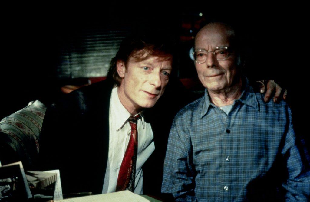 """Cassiel sitzt an der rechten Seite von Konrad, legt ihm den linken Arm über die Schulter und erzählt ihm """"In weiter Ferne, so nah!"""" dessen Lebensgeschichte. Konrad wird gespielt von Heinz Rühmann in seiner letzten Rolle."""