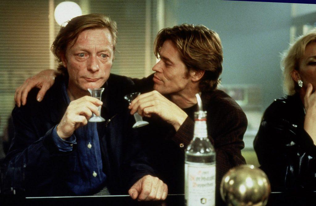 """Der Mensch gewordene Cassiel, gespielt von Otto Sander, sitzt an einer Bar, an seiner linken Seite, den rechten Arm über Cassiels Schultern gelegt, sitzt die von Willem Dafoe gespielte Figur Emit Flesti, im Film """"In weiter Ferne, so nah!"""" die Verkörperung der Zeit. Sie verführt Cassiel zum Trinken, beide halten Schnapsgläser in den Händen. Auf dem Tresen steht eine Flasche Doppelkorn."""