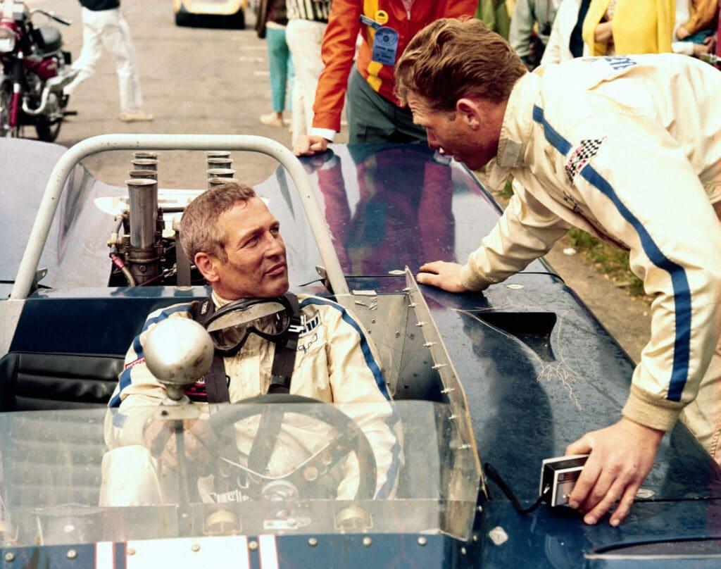 Frank, gespielt von Paul Newman, sitzt in seinem Rennwagen und berät sich beim Boxenstopp mit einem Mechaniker.