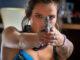 Arielle (Bella Thorne) richtet während eines Überfalls ihre Pistole auf die anwesenden Bankkunden. Infamous (2020)