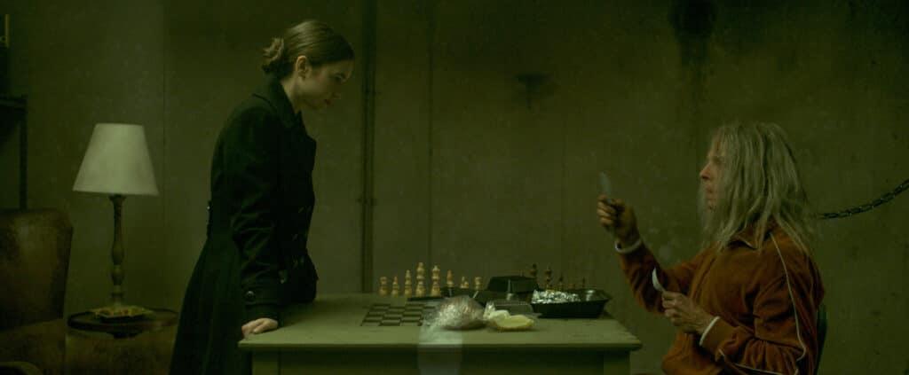"""Lauren (Lily Collins) lernt Morgan (Simon Pegg) kennen in """"Inheritance - Ein dunkles Vermächtnis"""". Während die in schwarz gekleidete Collins auf der linken Seite von einem Tisch steht, sitzt Pegg auf der anderen Seite des Tischs. Er hält dabei ein Plastikbesteck in beiden Händen, während er durch eine Halsfessel an der Wand hinter ihm angekettet ist. Vor ihm scheint eine Mahlzeit zu stehen. Im Hintergrund des Tischs ist zudem ein Schachspiel zu sehen."""