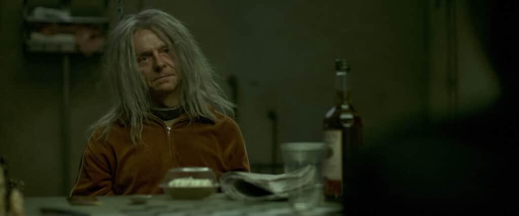 Der eingesperrte Morgan sitzt in Inheritance - Ein dunkles Vermächtnis an einem Tisch auf dem unter anderem eine Flasche mit Alkohol sowie eine Zeitung und eine Kleinigkeiten zu Essen stehen. Er selber trägt ein orangenes Oberteil und lange graue strohige Haare. Sein Gesicht sieht sehr abgemagert aus. Um den Hals trägt eine Halsfessel aus Metall.