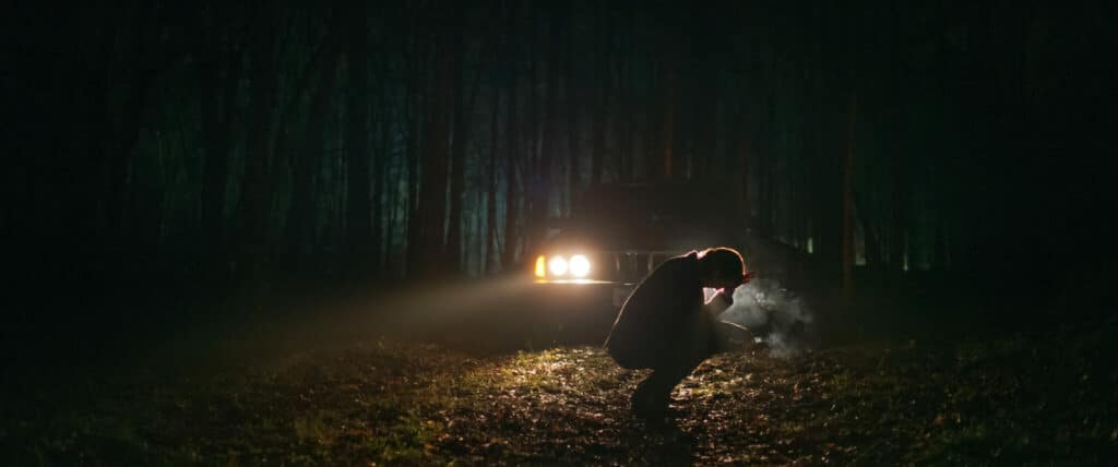 Lauren hockt inmitten eines dunklen Waldes. Lediglich die Scheinwerfer ihres Wagens erleuchten ein wenig den Schauplatz eines mit herbstlichen Blättern bedecken Gebiets.
