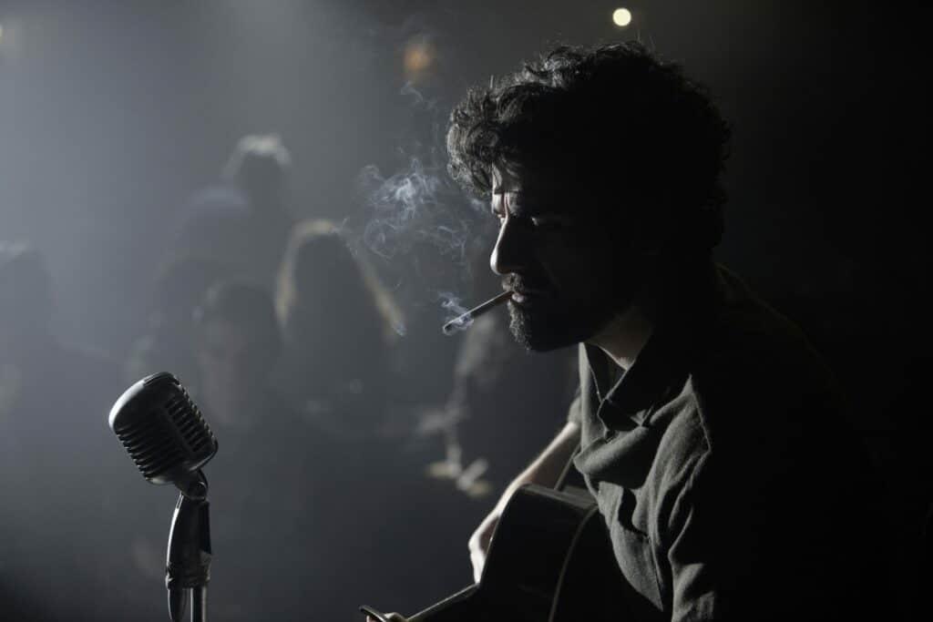 Auch Oscar Isaac (hier in Inside Llewyn Davis) war Thema im Filmtoast Adventsfrühstück Podcast #2. Auf dem Bild sieht man den Schauspieler auf einer Bühne rauchend Gitarre spielen.