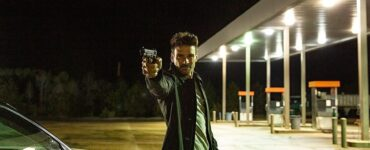 Sloan, gespielt von Frank Grillo, steht mit gezückter Pistole an einer Tankstelle.