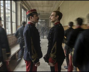Die zwei Protagonisten von Intrige, Marie Georges Picquart (Jean Dujardin) und Alfred Dreyfus (Louis Garrel), stehen sich in einem Gang gegenüber und blicken sich bestimmt in die Augen. Um sie herum sind unscharf weitere Mitglieder der französischen Armee zu erkennen.