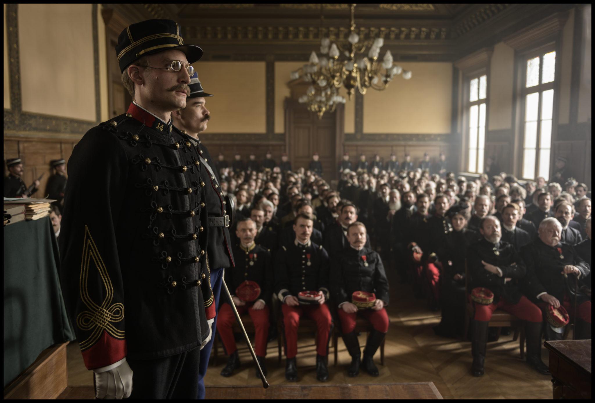 In einem Gerichtssaal steht vorne links im Bild der Angeklagte Alfred Dreyfus stramm in Militäruniform. Im Hintergrund sind unscharf einige Verschwörer der Dreyfus-Affäre und Zuschauer des Gerichtsprozesses auf Stühlen sitzend zu sehen.