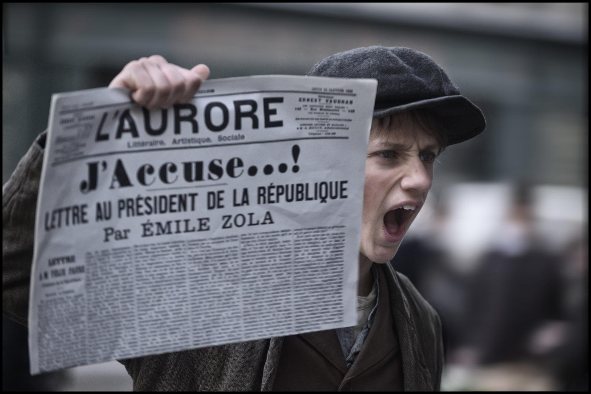 """Ein Junge hält in Intrige die Zeitung L'Aurore hoch, in der der Journalist Émile Zola seine Anklageschrift """"J'accuse"""" veröffentlicht hat."""