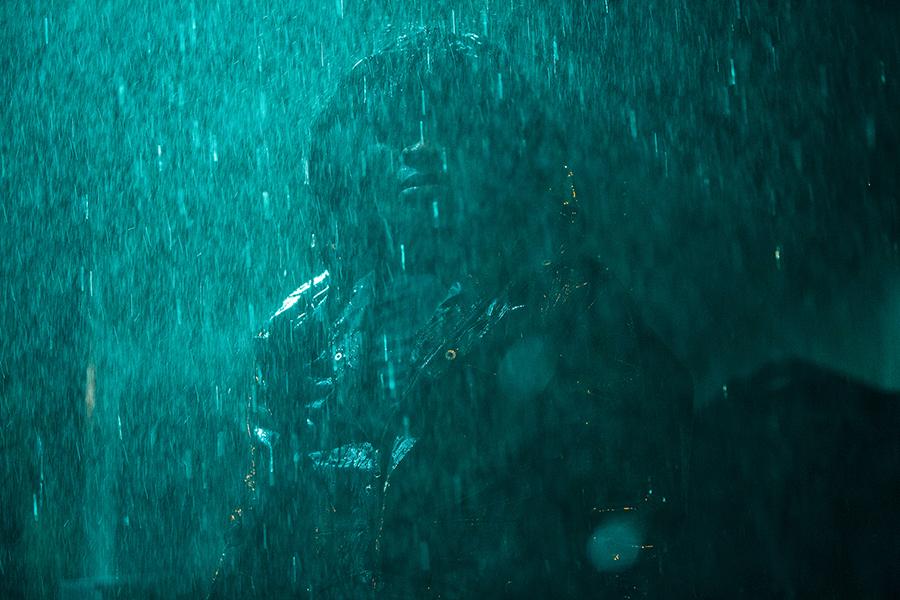 Ein Mann mit Regenjacke und Kapuze steht nächstens im Regen in Invincible Dragon. Sein Gesicht ist nicht in Gänze zu erkennen.