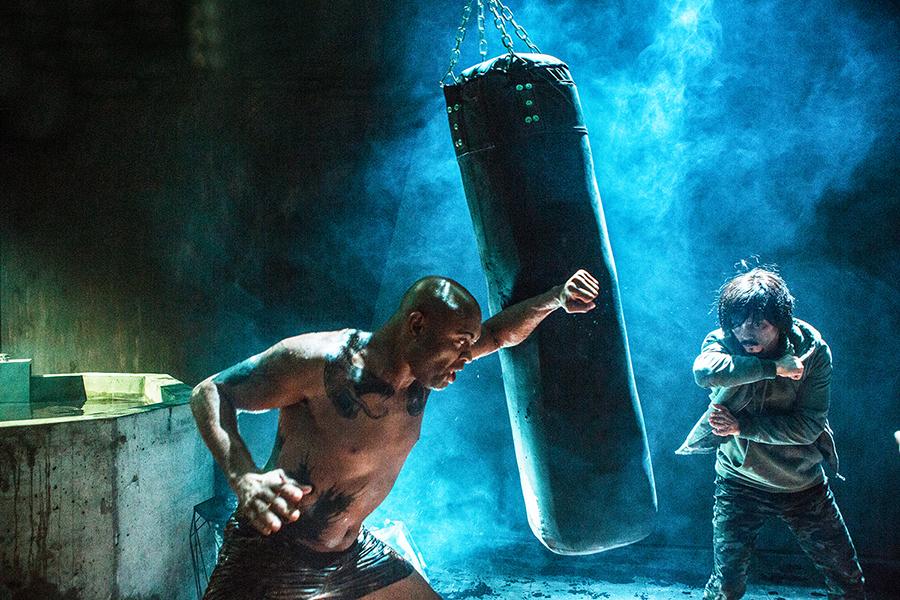 Alexander Sinclair schlägt auf einen Box-Sack ein, ihm gegenüber wartet der ungepflegte Kow Loon in Invincible Dragon.