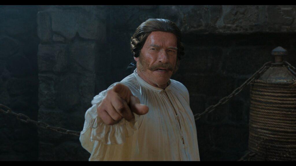 Arnold Schwarzenegger zeigt als Gefängniswärter James Hook auf seine Gegner.