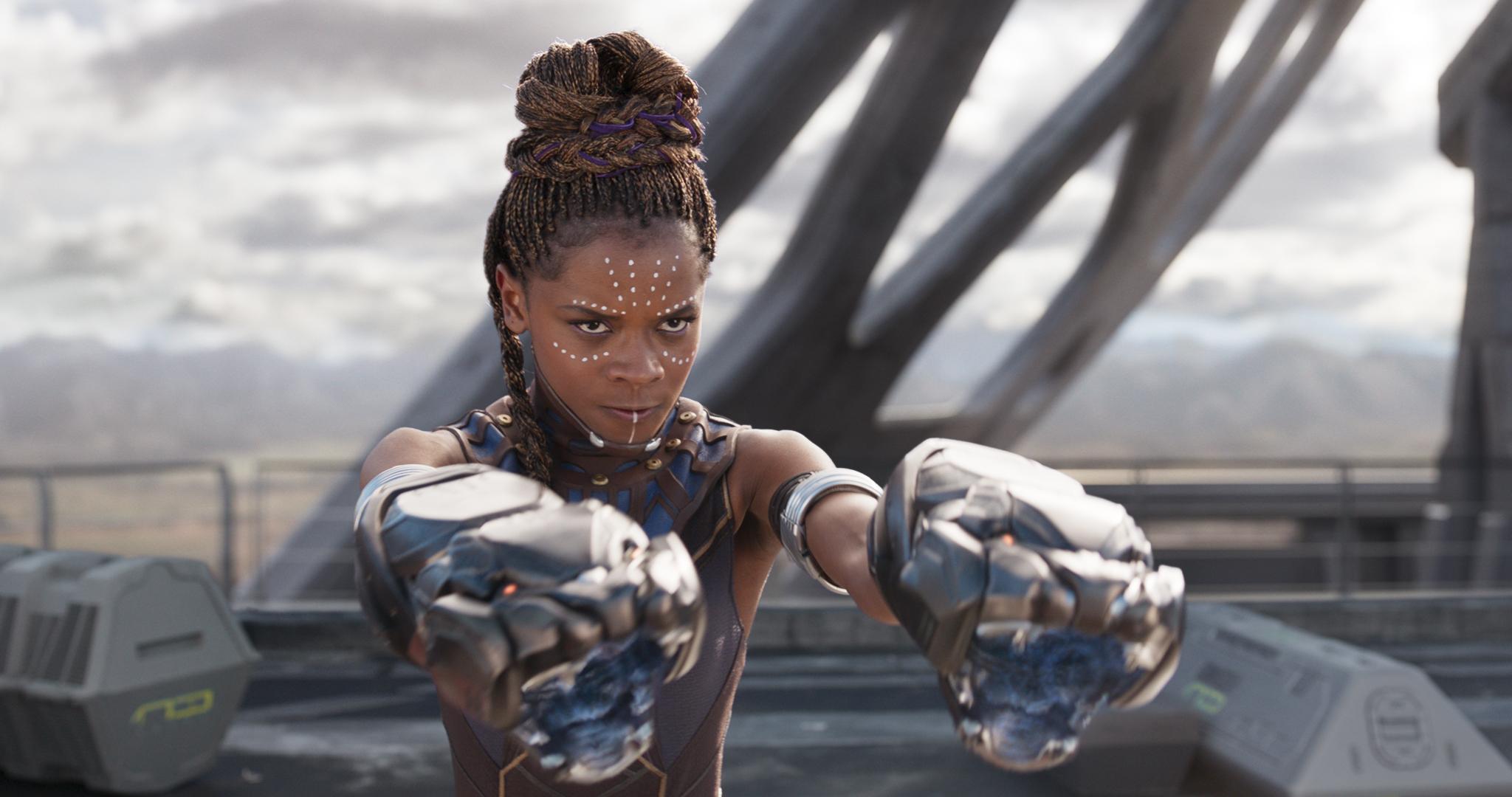 Shuri (Letitia Wright) hebt ihre Arme. An ihren Händen hat sie Waffen in Form von Schlangenköpfen.