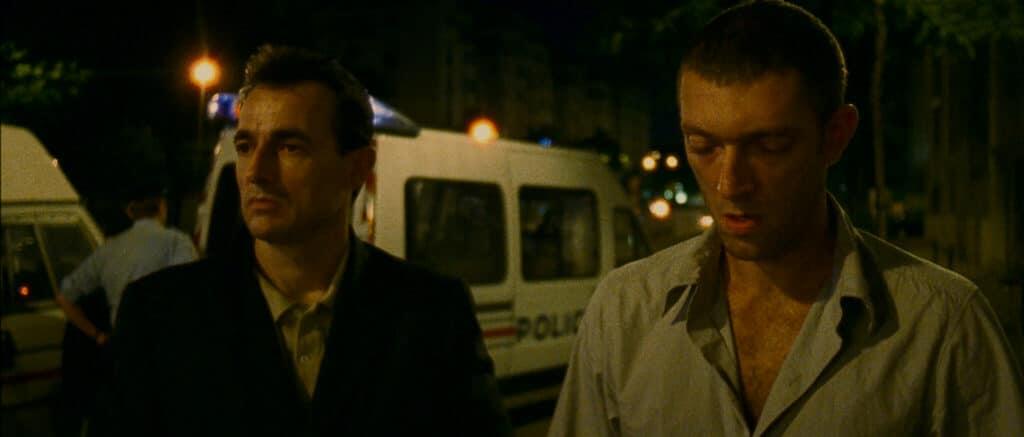 Marcus und Pierre stehen in Irreversibel desillusioniert am Tatort, hinter ihnen stehen Polizei- und Krankenwagen. Im Hintergrund leuchten Lichter des städtischen Nachtlebens.