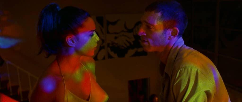 Alex und Marcus haben eine Auseinandersetzung auf einer Party. Das dunkel gehaltene Bild ist nur von Partylichtern erhellt.