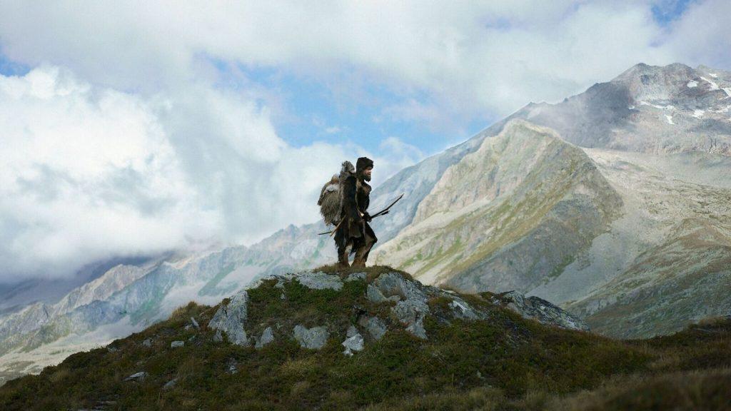 """Jürgen Vogel in """"Der Mann aus dem Eis"""" auf einer Bergspitze und im Hintergrund sind wolkenverhangene Berge © Ascot Elite Home Entertainment"""