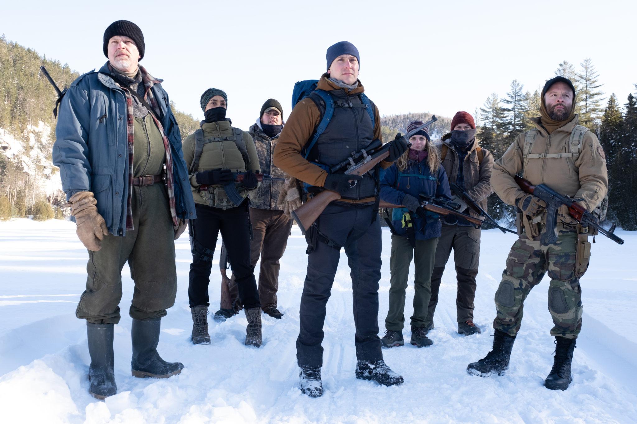 Die komplette Gruppe der Teilnehmer steht mit Ausrüstung und Bewaffnung auf einer großen Schneefläche
