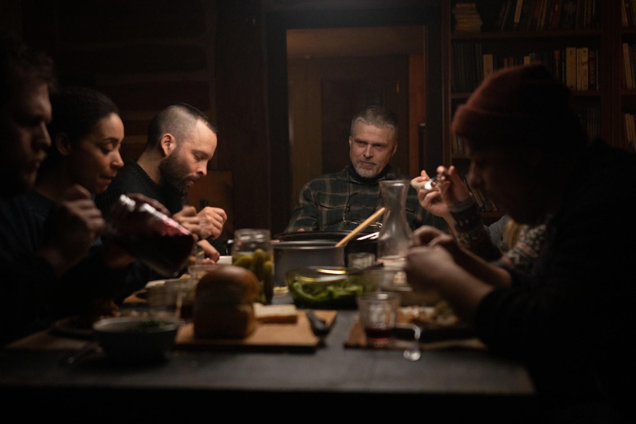Die Teilnehmer sitzen beim Abendessen zusammen an einem Tisch, am Kopf sitz der Trainer des Camps, auf dem Tisch diverse Speisen