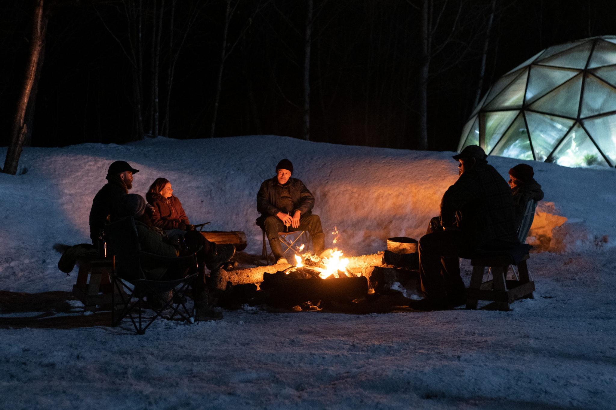 Die Camper sitzen in der Dunkelheit um ein Lagerfeuer in Bis zum Untergang