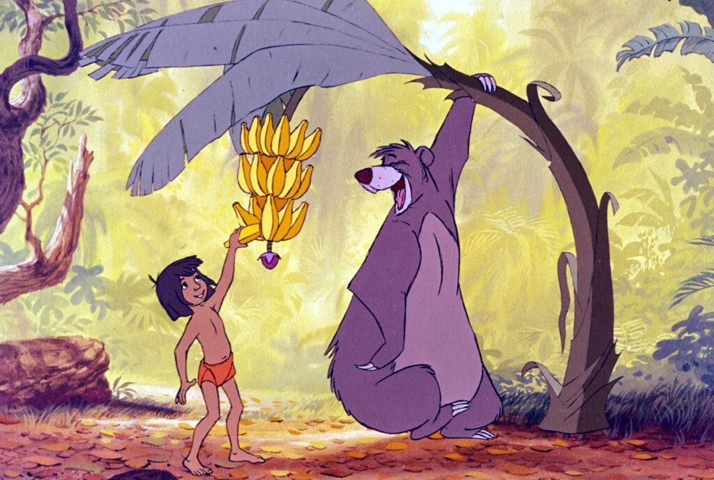 Balu hängt sich an einen Bananenbaum, damit Mogli eine der Früchte pflücken kann - Szene aus Das Dschungelbuch, ein Film von Disney.