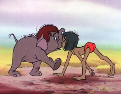 Mogli marschiert auf allen Vieren und stößt mit einem jungen Elefanten frontal, Nase an Nase, zusammen.