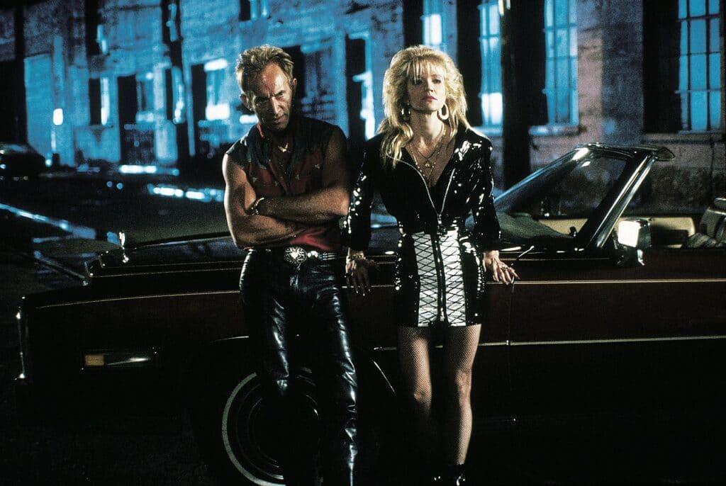 Im schillernden New Orleans zur Nacht lehnen Lance Henriksen und Ellen Barkin ungeduldig am Auto in Johnny Handsome.