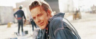 Mickey Rourke lehnt sich in der Arbeitspause auf den Tisch und raucht eine Zigarette in Johnny Handsome.