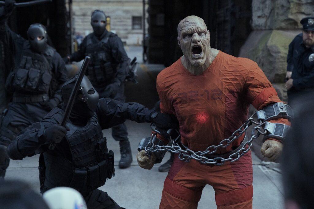 Ein missgestalteter Bösewicht im orangen Häftlings-Suit kann kaum von den schwarz gekleideten Polizisten gebändigt werden - Neu auf Netflix im Mai 2021